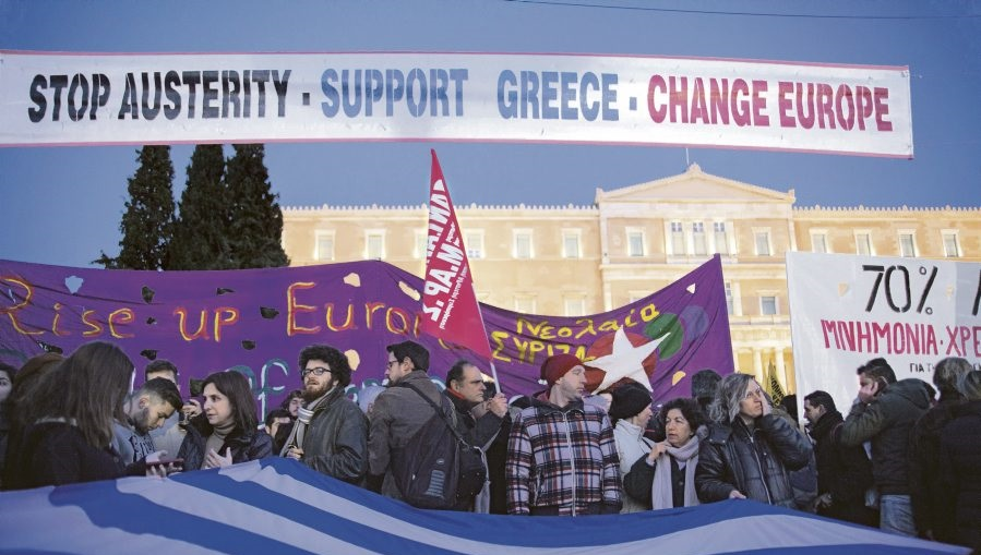 "Greek flag and banner ""Stop Austerity Support Greece Change Europe"" during support protest for Greece in front of Parliament in Athens. Greeks protest against austerity policy of Europe and Germany. Greeks support negotiation of Greek PM during Eurogroup i (c)Picture-Alliance/AFP"