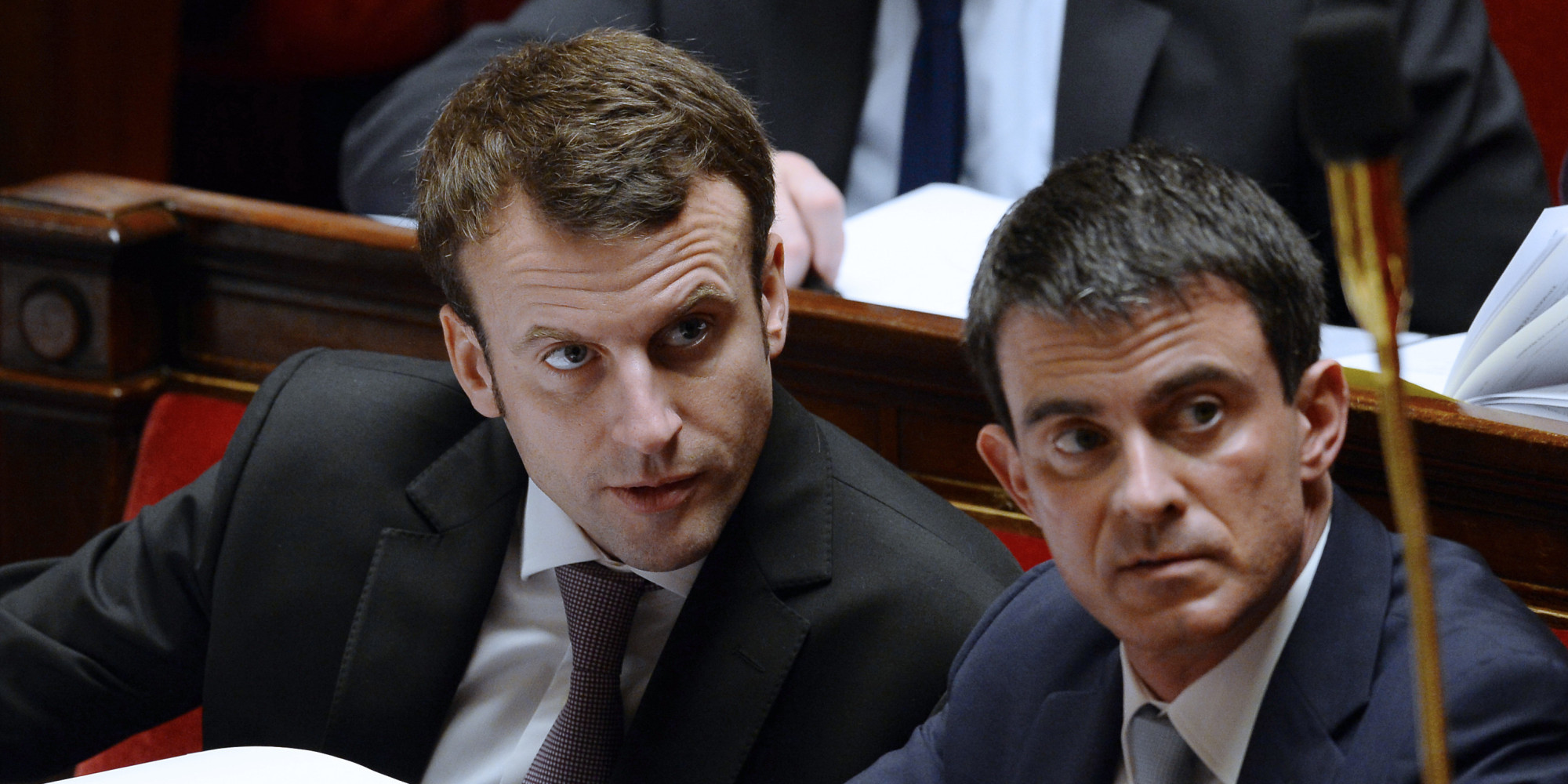 "French Economy and Industry Minister Emmanuel Macron (L) speaks with Prime minister Manuel Valls as they attend a working session on the Macron's law at the French National Assembly in Paris on February 14, 2015. Macron is trying to push through a controversial series of laws that he hopes will, in his words, ""unblock"" France's economy, which is suffering from high unemployment and sluggish growth. These include a proposal to allow shops to open on up to 12 Sundays a year instead of the current five.  AFP PHOTO / ALAIN JOCARD"