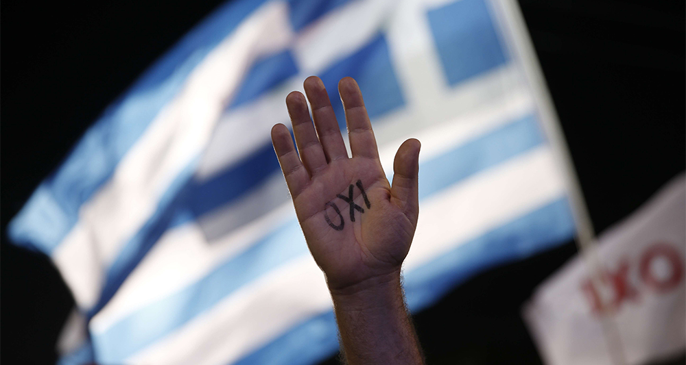 A demonstrator rises his hand reading the word ''No'' as a Greek flag waves during a rally organized by supporters of the No vote in Athens, Friday, July 3, 2015. A new opinion poll shows a dead heat in Greece's referendum campaign with just two days to go before Sunday's vote on whether Greeks should accept more austerity in return for bailout loans. (AP Photo/Petros Giannakouris)/XTS181/346019185476/1507032125