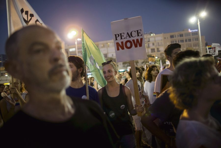 Left-wing protesters hold signs during a protest condemning Friday's arson attack in the West Bank, at Rabin square in Tel Aviv August 1, 2015. Some 3,000 demonstrators gathered for the rally organised by the Israeli anti-settler group Peace Now against the attack by suspected Jewish assailants who torched a Palestinian home in the occupied West Bank on Friday, killing an 18-month-old toddler and seriously injuring three other family members, an act that Israel's prime minister described as terrorism. REUTERS/Baz Ratner