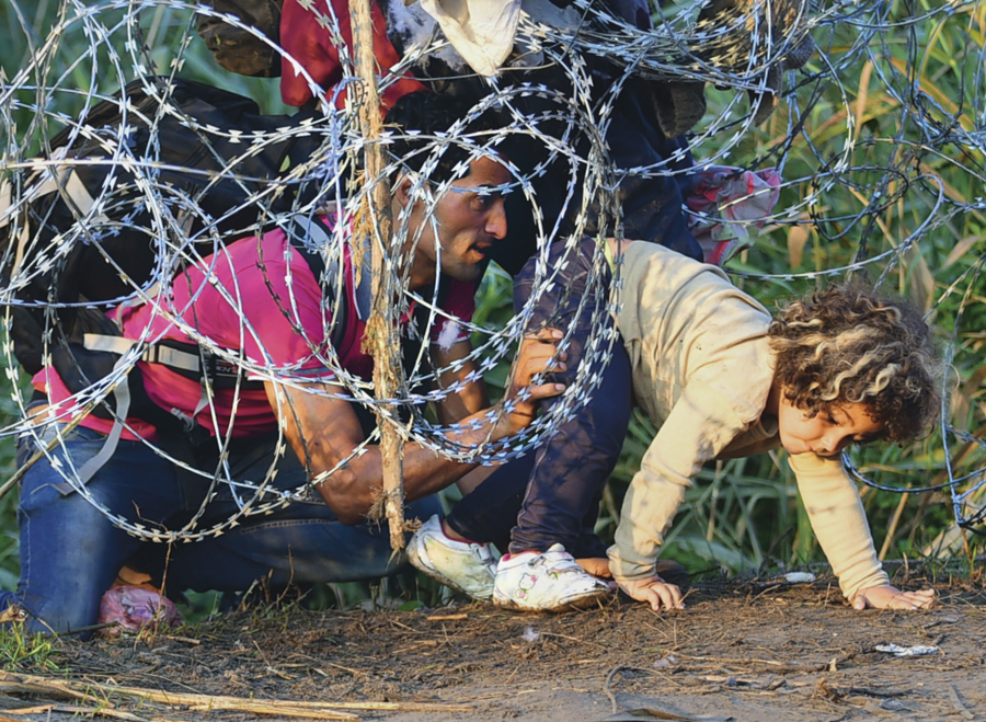 CORRECTING THE BYLINE A young girl of a migrant's family is helped by her father as they creep under a barbed fence near the village of Roszke, at the Hungarian-Serbian border on August 27, 2015. As Hungary scrambles to ramp up defences on its border with Serbia, refugees continued to surge into the country in record numbers, police figures confirmed. AFP PHOTO / ATTILA KISBENEDEK