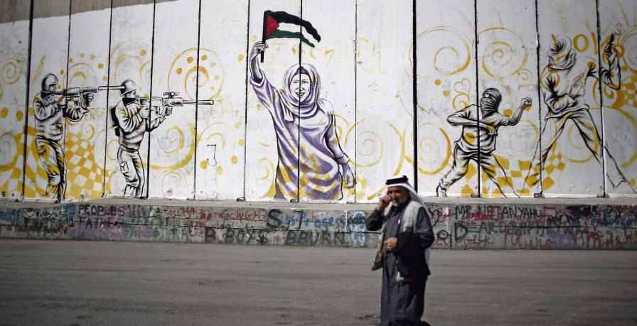 A Palestinian man walks past graffiti sprayed on Israel's controversial separation wall in the West Bank city of Bethlehem, on October 22, 2015. AFP PHOTO / THOMAS COEX