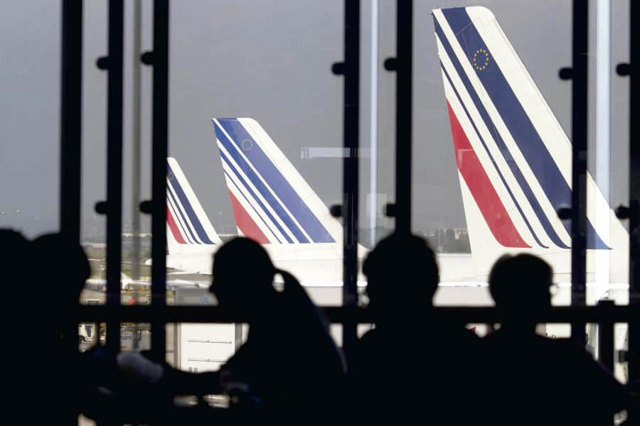 "(FILES) A file picture taken on September 15, 2014 shows passengers waiting in a lounge as Air France planes are seen behind at Paris-Orly airport in Orly. On June 22, 2015 Air France and the pilots union SNPL will meet at the High Court of Bobigny where the company sued the union after their opposition to the restructuring plan called ""Transform"". AFP PHOTO / KENZO TRIBOUILLARD"