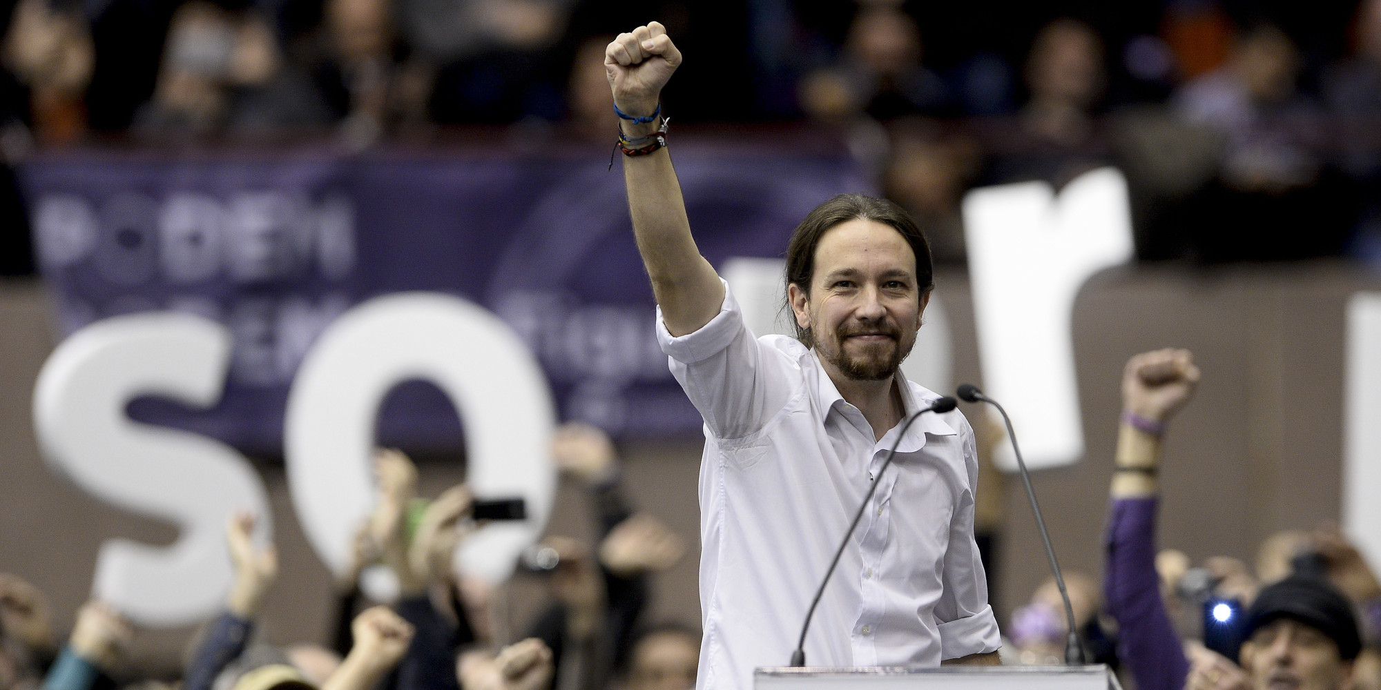 """Leader of Podemos, a left-wing party that emerged out of the """"Indignants"""" movement, Pablo Iglesias, holds up his fist at a party meeting on December 21, 2014 in Barcelona. Spain's conservative ruling party and the opposition Socialists are in panic mode as a surge in support for upstart Podemos shows little signs of abating ahead of elections next year. Less than a year since it was founded by the leaders of the Indignants movement, Podemos, with its pledge to defend the poor and bring to heel the elite """"caste"""" of politicians and bankers, is leading opinion polls. AFP PHOTO/ JOSEP LAGO"""