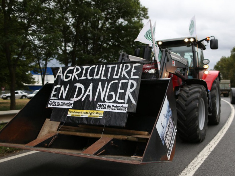 "A protester drives a tractors with a placard reading ""Agriculture in danger"" in Verson, near Caen in northwestern France, on July 19, 2015, during a demonstration by farmers against the price at which they sell their product and the selling prices set by supermarkets.  AFP PHOTO / CHARLY TRIBALLEAU"
