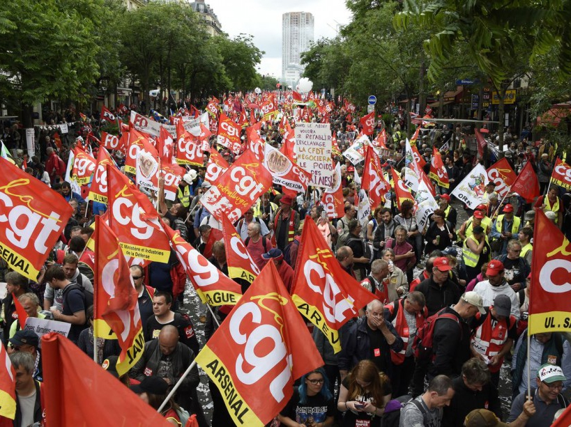 People wave flags of French union confederation Confederation generale du travail (CGT) during a demonstration against proposed labour reforms in Paris on June 14, 2016.  Strikes closed the Eiffel Tower and disrupted transport in France on June 14 as tens of thousands prepared to march against labour reforms with the Euro 2016 football championship in full swing.  / AFP PHOTO / DOMINIQUE FAGET